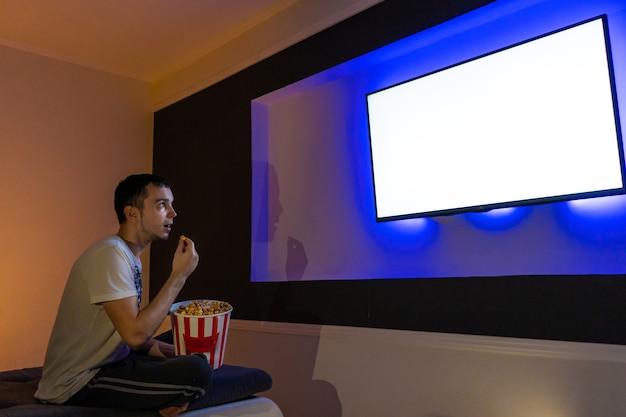 La persona guarda un film seduta sul divano con un secchio di popcorn.