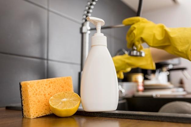 Persona che indossa guanti di protezione utilizzando prodotti per la pulizia
