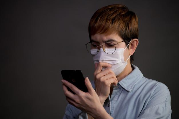Persona che indossa una maschera chirurgica e usa il telefono con aria preoccupata e preoccupata per l'epidemia di pandemia e notizie dai social media