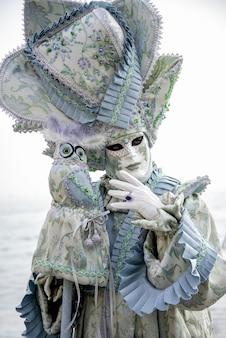 La persona indossa la maschera di carnevale e il costume blu decorato con il gufo del giocattolo sulla sua mano che posa al carnevale nella celebrazione di venezia, italia