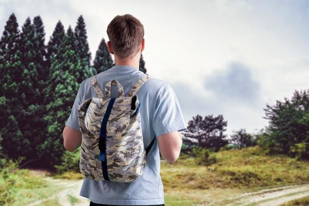 Una persona con lo zaino che fa trekking e si arrampica sulla cima della montagna
