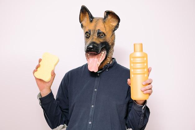 La persona con la maschera del cane mostra la spugna e il gel da bagno