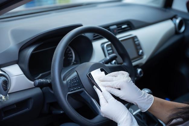 Persona con i guanti che pulisce telefono cellulare dentro l'automobile