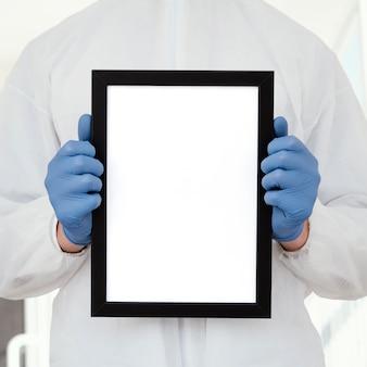 Persona con mascherina medica che tiene una compressa in bianco