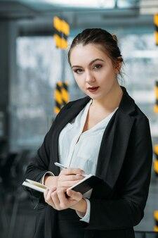 Ritratto di assistente personale. la pianificazione aziendale conta. giovane donna che prende appunti ascoltando le istruzioni del capo virtuale.