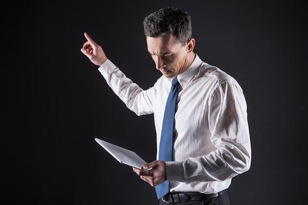 Gadget personale. piacevole uomo adulto simpatico in piedi e indicando il pannello sensoriale mentre guarda lo schermo del tablet
