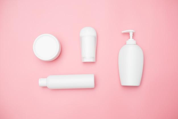 Vasetti di prodotti per l'igiene personale bianchi su sfondo rosa, copia spazio, vista dall'alto. foto di alta qualità