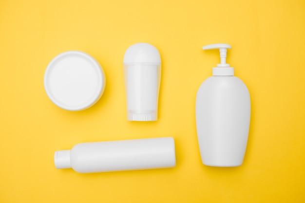 Vasetti di prodotti per l'igiene personale bianchi su sfondo giallo, copia spazio, vista dall'alto. foto di alta qualità