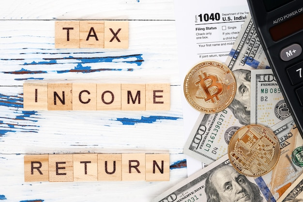 Modulo di imposta sul reddito personale 1040, banconote da un dollaro, bitcoin e calcolatrice.