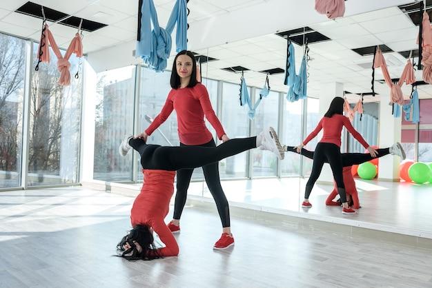 Personal trainer che assiste la donna in fase di riscaldamento per esercizio fitness nella luminosa palestra. uno stile di vita sano