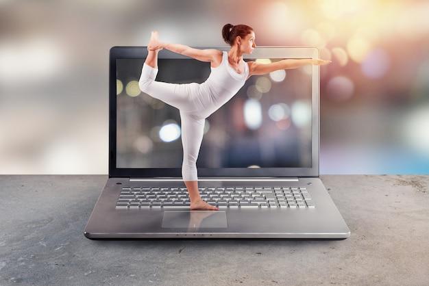 Il personal trainer fa lezioni di yoga in palestra tramite internet e laptop