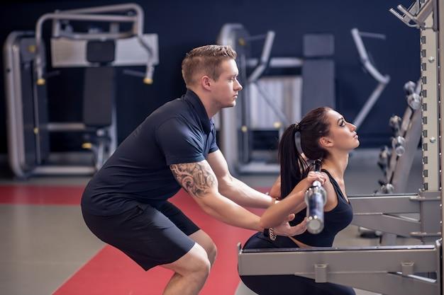 Personal trainer e donna adatta che lavora con il bilanciere