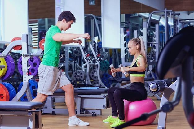 Personal trainer e ragazza con manubri facendo esercizi