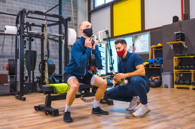 Personal trainer in palestra che corregge gli squat del giovane atleta nella pandemia di coronavirus