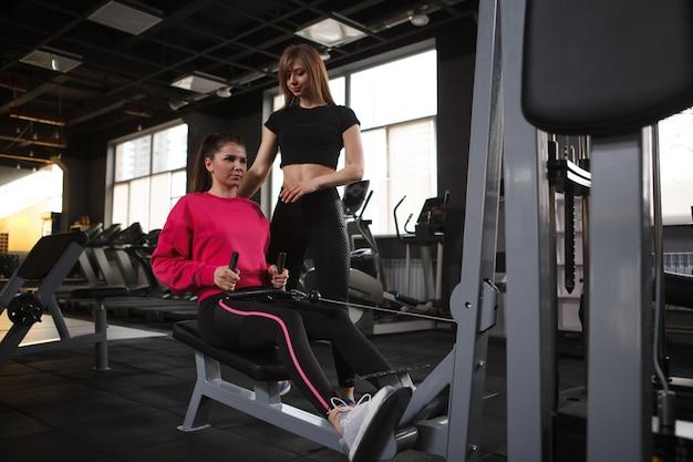Personal trainer e il suo cliente utilizzando una macchina da palestra per fila di cavi seduti