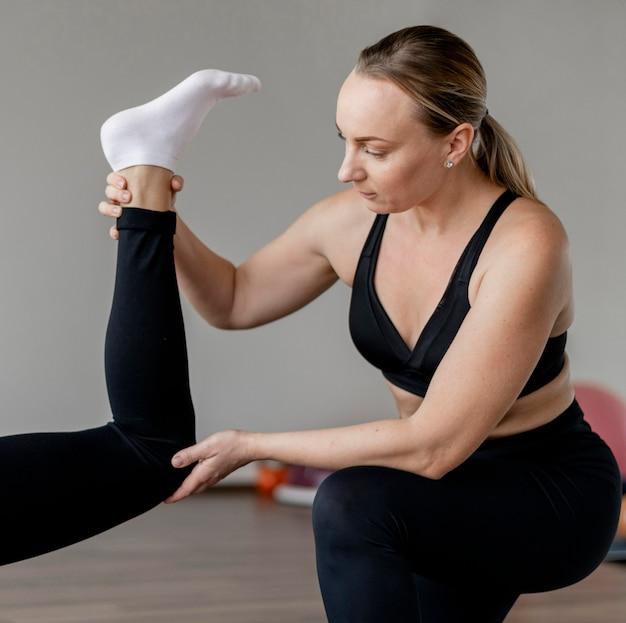 Personal trainer che tiene la gamba di un cliente