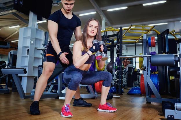 Istruttore di personal trainer aiuta a fare esercizi per lo sport gi
