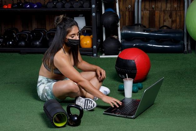 Personal trainer saluta il computer dopo aver tenuto una lezione online bevendo un drink