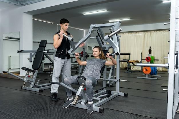 Personal trainer che lavora con una donna giovane e bella