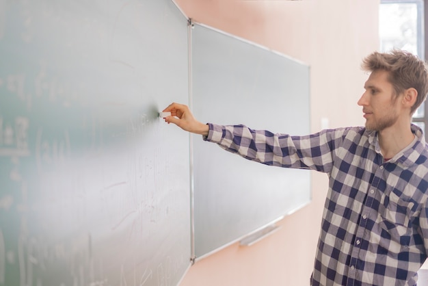 Le persone tengono in mano il gesso e scrivono calcoli matematici su una lavagna b