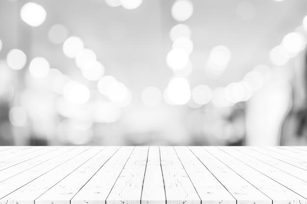 La tavola di legno bianca vuota di prospettiva sopra supera il fondo della sfuocatura