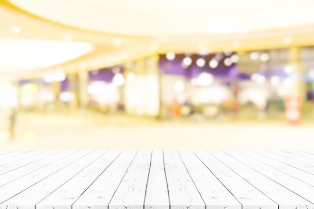 Tavolo in legno bianco vuoto prospettiva in alto sopra sfocatura dello sfondo