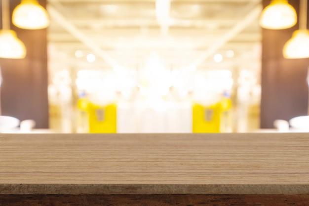 La tavola di legno vuota di prospettiva sulla cima sopra il fondo della sfuocatura, può essere usata per l'esposizione dei prodotti del montaggio