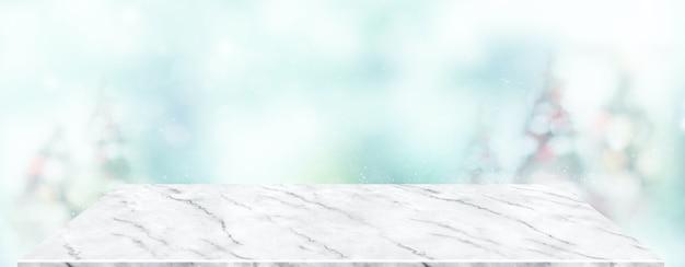 Il tavolo in marmo prospettico con sfocatura dell'albero di natale decora la luce delle corde e il bokeh blu