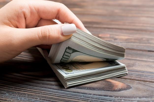 Vista prospettica delle mani di una donna d'affari contando cento banconote in dollari su fondo di legno