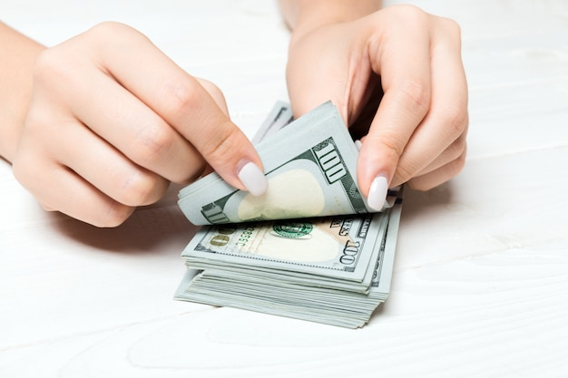 Vista prospettica delle mani di una donna d'affari contando cento banconote in dollari sul tavolo di legno. concetto di successo e ricchezza