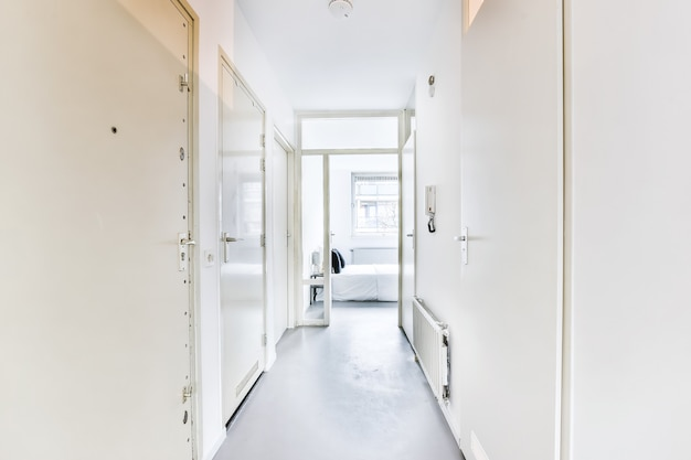 Vista prospettica del corridoio stretto vuoto con pareti bianche e porta aperta che conduce alla camera da letto in appartamento moderno in stile minimalista