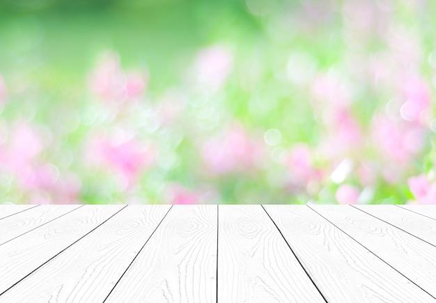 Legno bianco di prospettiva sopra il fondo del giardino e dei fiori della sfuocatura