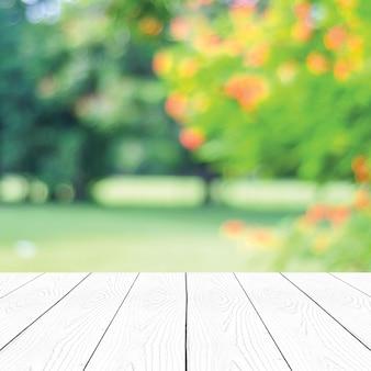 Prospettiva in legno bianco e sfocatura dello sfondo del parco naturale all'aperto