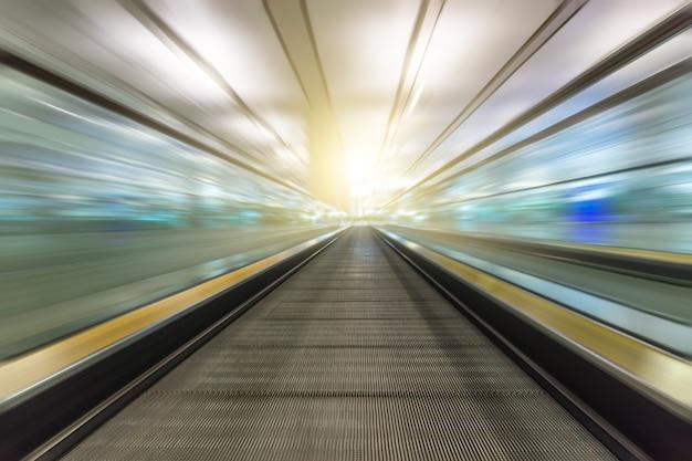 Prospettiva grandangolo in bianco e nero della moderna luce blu illuminata e spaziosa ad alta velocità mobile scala mobile con veloce percorso offuscata di corrimano nel movimento di traffico vanishing