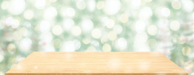 Il tavolo in legno prospettico con sfocatura dell'albero di natale decora la luce delle corde