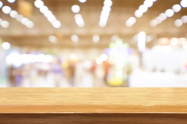 Tavola di legno di prospettiva sulla cima sopra il fondo della caffetteria della sfuocatura
