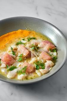 Piatto di cucina peruviana. ceviche di branzino con pompelmo e salsa gialla, servito in un piatto grigio su marmo