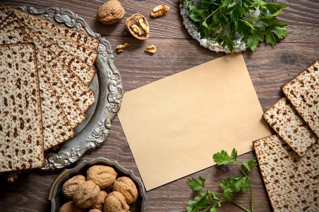 Sfondo di pesach. ebraico pasquale. matzah, bottiglia di vino, noci, prezzemolo sul tavolo di legno e cartello bianco. spazio per il testo.