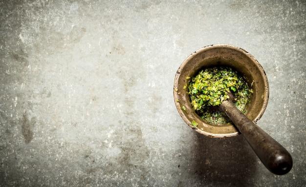 Pesto in un mortaio con pestello sul tavolo di pietra.