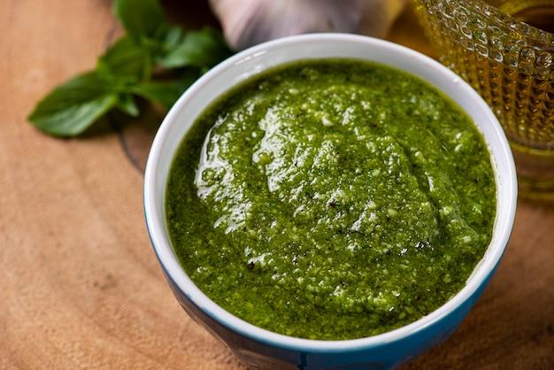 Pesto in una ciotola con gli ingredienti in sottofondo. olio d'oliva, aglio e basilico.