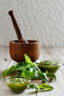 Pesto e basilico fresco su tavola di legno