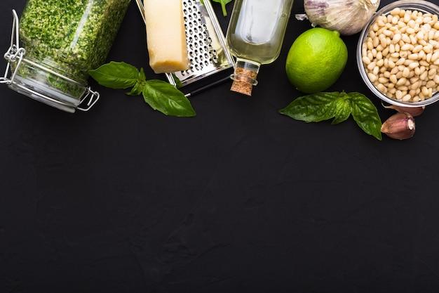 Pesto in barattolo di vetro e ingredienti per fare il pesto. lay flat con copia spazio per il testo