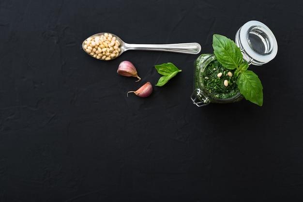 Pesto in barattolo di vetro con ingredienti: pinoli, basilico verde, aglio su fondo di cemento scuro. pesto italiano per pasta, spaghetti, bruschette. vista dall'alto, distesi con spazio di copia per il testo