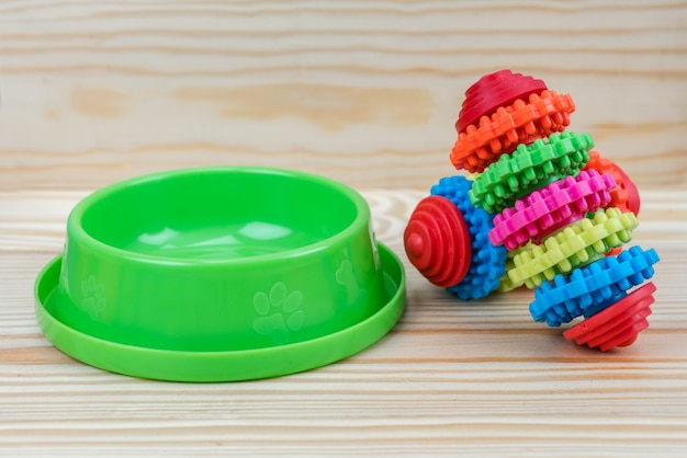 Ciotola dell'animale domestico con il giocattolo di gomma con lo spazio della copia su legno