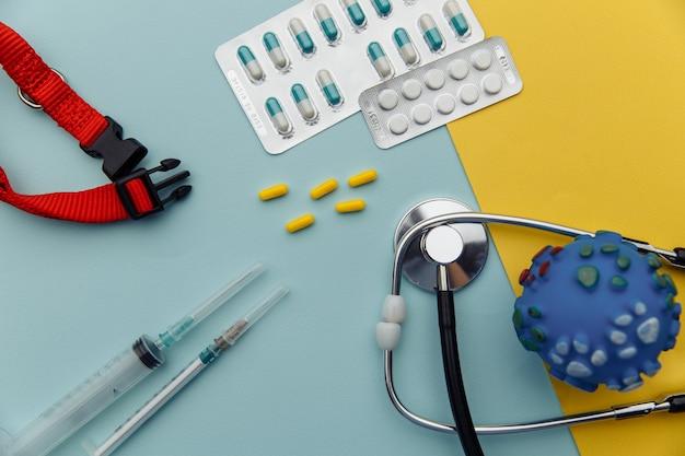 Concetto di cura degli animali domestici. pillole, ampolla, siringa e collare su un tavolo giallo blu.