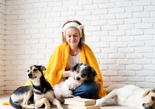 Cura degli animali. giovane donna sorridente divertente in plaid giallo che si siede con i suoi cani che leggono un libro