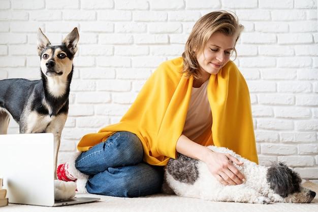 Cura degli animali. giovane donna divertente in plaid giallo che si siede sul pavimento con i suoi cani
