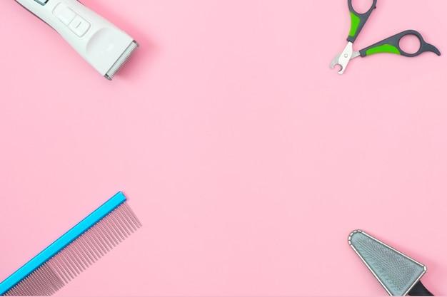 Strumenti per la cura e la toelettatura degli animali domestici su uno sfondo rosa. concetto di cura e igiene degli animali domestici. copia spazio, posto per il tuo testo. modello