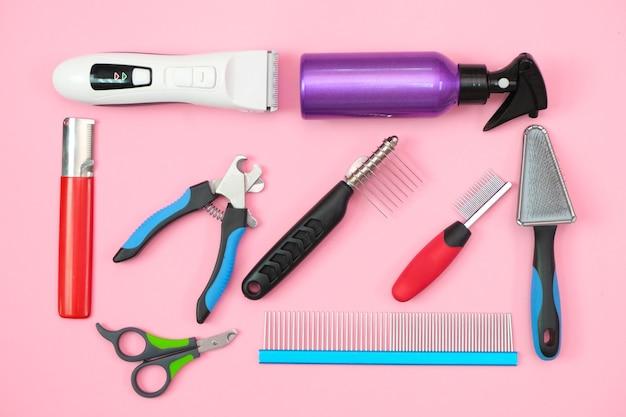 Strumenti per la cura e la toelettatura degli animali domestici su uno sfondo rosa. concetto di cura e igiene degli animali domestici