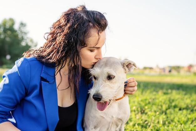 Cura degli animali. adozione di animali domestici. giovane donna che bacia il suo cane di razza mista